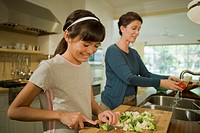Grandmother and granddaughter chopping vegetables in the kitchen