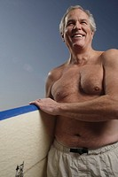 Mature man holding a surfboard