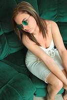 Young woman sitting on her sofa, wearing sunglasses