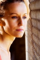 A portrait of a beautiful young woman looking out through a fence