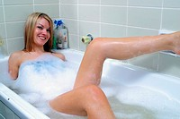 A young blonde woman relaxing in a bubble bath