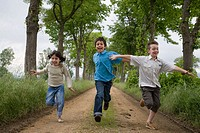 Children running by tree-lined path. Arkaute, Alava, Euskadi, Spain