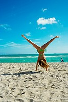 Young woman doing cartwheels in the sand