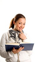 Teenage girl smiling at the camera while holding book