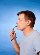 Man biting his glasses while thinking