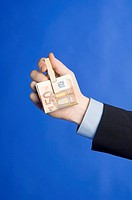 Businessman holding banknotes clipped with a wooden peg