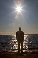 Businessman standing on the rocks enjoying sunrise