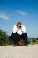Stressed businessman sitting on briefcase by the roadside