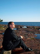 Businessman sitting on the rocks, contemplating