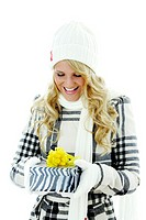 Woman in winter clothing smiling while looking at a box of present