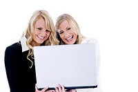 Businesswomen laughing while using laptop together