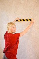 Woman smiling at the camera while taping the wall with an adhesive tape