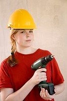 Teenage girl with safety helmet holding a drill