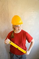 Teenage girl with safety goggles and helmet holding spirit level