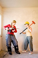 Women with sledge hammer and drill