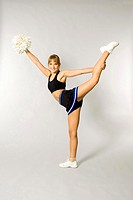 Teenage girl lifting up one leg while holding pom-pom