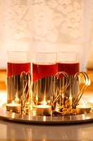 Mulled wine in glasses with decorative holder and lit tealights (thumbnail)