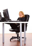 Businesswoman sitting with legs on the office table while talking on the mobile