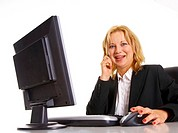Businesswoman working on the desktop while talking on the mobile