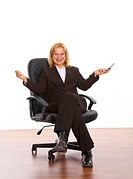 Happy businesswoman sitting on office chair with arms open and holding mobile