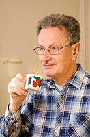Senior man with glasses holding cup
