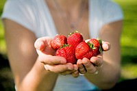 Woman with a handful of strawberries