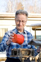 Senior man pouring bird food into bird house