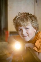 Boy flashing flashlight at the camera