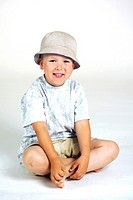 Boy with hat sitting on the floor smiling at the camera