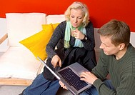 Man and woman using laptop together