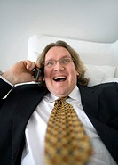 Businessman talking happily on the phone while lying on the couch (thumbnail)