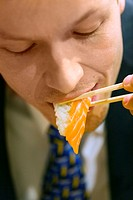 Businessman eating salmon sushi with chopsticks (thumbnail)