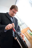 Businessman opening a bottle of wine