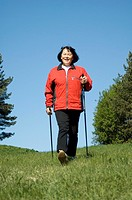 Senior woman strolling with walking sticks outdoors