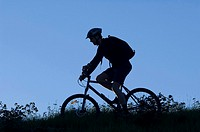 Silhouette of man riding on the bicycle