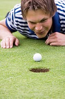 Man lying down looking at golf ball