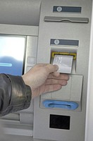 Hand inserting card into ATM