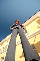 Businesswoman standing with arms akimbo looking down at the camera