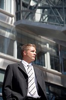 Businessman posing outdoors in front of a building