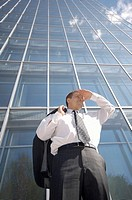 Businessman shielding his eyes while looking into the distance (thumbnail)