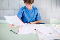 Boy in Classroom Looking at Paperwork