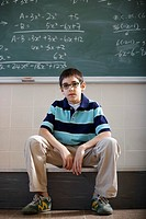 Pre-Teen Boy Sitting by Blackboard