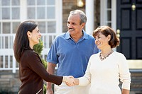 Senior Hispanic couple shaking hands with realtor (thumbnail)