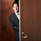 Mixed Race businessman walking through doorway