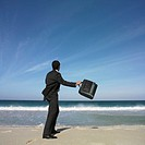 Hispanic businessman throwing briefcase at beach