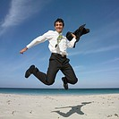 Hispanic businessman jumping on beach
