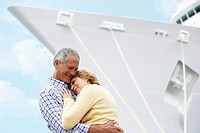 Middle Aged Couple Hugging Beside a Cruise Ship