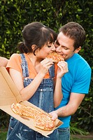 Multi-ethnic couple eating pizza