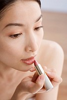 Asian woman applying lipstick