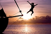 Girl jumping from yacht in sundown. Bora Bora. French Polynesia